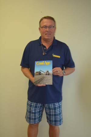 Sam Bennett poses with 'Coal Age' magazine, a national publication about the coal mining industry, which highlighted the Coshocton Coal Miners Memorial in its September issue.