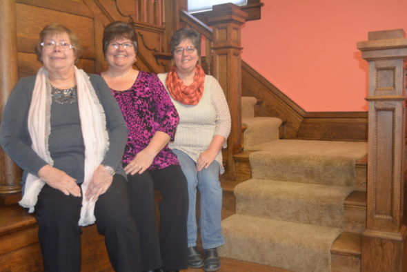 Sisters Jacque Wagner and Vickie Davis recently purchased the building at 204 S. Fourth St. to create a quilting retreat, which will open soon. They named the retreat after their mother. Pictured from left to right are: Sharon Henry, Davis, and Wagner sitting by the old staircase in the house with original woodwork.