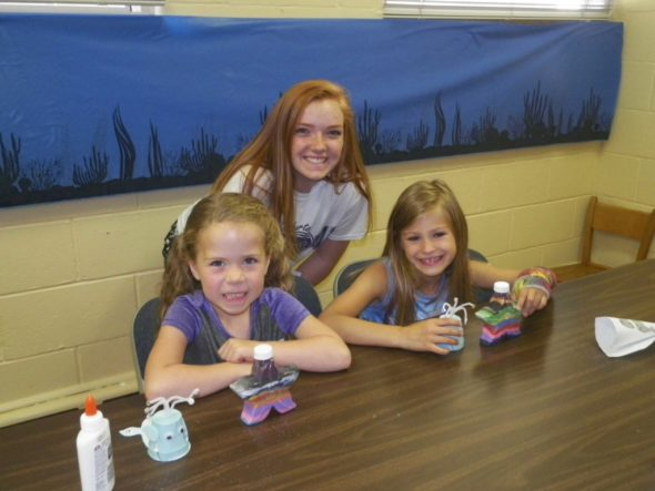 Karaline Graham, 6, and Kylee Bice, 7, show off the crafts they made with the help of their junior leader, Grace Miller, at the Cloverbud Day Camp held at Grace UMC on June 17.
