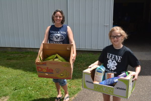 Coshocton Kiwanis Club President Tabitha Patterson and Keene Kountry Club 4-H member Lydia Black are pictured carrying items to a vehicle at the free produce market on June 29 at the fairgrounds. The Kiwanis Club contracts with Mid-Ohio Food Bank for these markets and has now held three of them. Josie Sellers | Beacon