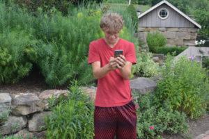 Adam Alvarez is pictured using his phone at Clary Gardens to play Pokémon Go. Josie Sellers | Beacon