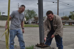 Century National Bank donated the light poles that were on the site of the bank's additional Coshocton branch which will be located on North Third Street following construction. Pictured are Hubie Cushman, (left) Indian Mud Run organizer and Vic Allen of Allen Construction who donated his time and equipment to remove the light poles. The poles will be used for an obstacle on the Indian Mud Run course. Mark Fortune | Beacon