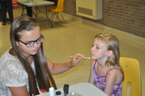 Face painting: McKenna Collins is pictured painting a kitty on 8-year-old Angel Kidd at the annual meeting of members for the Frontier Propane and Frontier Power Company held at River View High School on Friday evening, July 31. Beacon photo by Mark Fortune