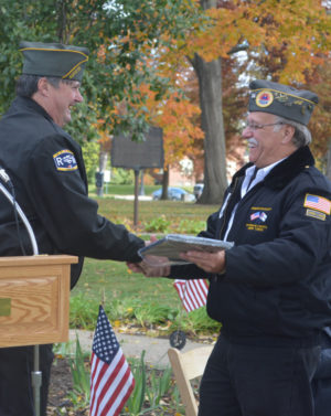 Veterans Service Officer Jim Barstow presented Herb Tidrick with a plaque honoring him for his dedication to helping veterans in our community. Tidrick retired from the veterans' service office on Nov. 11 and was the main speaker at the Veterans Day ceremony on the court square. Both Barstow and Tidrick are veterans of the U.S. Navy.  Josie Sellers | Beacon