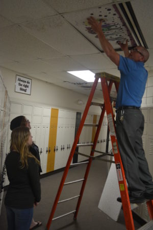 River View Junior High eighth graders Jennifer Roderick and Jessica Brooks watch as art teacher Rodney Stein installs the ceiling tile that Roderick decorated. Josie Sellers | Beacon