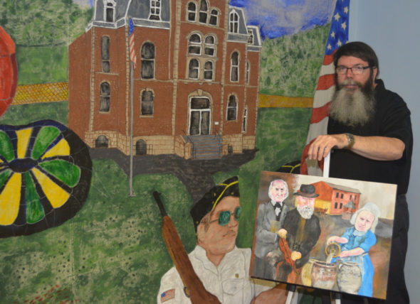 Ron Cummings will have his art work on display at the West Lafayette Branch Library during the month of June. He is pictured here with a painting he is working on and a mural he created that is on display in his classroom at the Church of Christ. Josie Sellers | Beacon