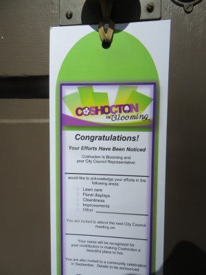 Recognition: Door hangers will be handed out to residents and businesses who are winners in the Coshocton is Blooming Community Pride Recognition program. Photo contributed to The Beacon