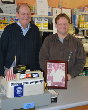 Ownership: Roger Eastman and Bill Potter stand behind a photo of Don Lessig, who is Eastman's father-in-law and a former owner of Fisher Decorating Center. Lessig sold the business to Eastman who recently retired and turned the reins over to Potter. Beacon photo by Josie Sellers