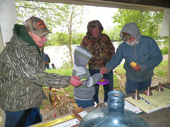 CCSA members Skip Lawrence, Kendall Woods and Ray Rogers offer small prizes to a young fisherman who had just had his catch measured at the CCSA Fishing Derby on May 6 at Lake Park. Jen Jones | Beacon