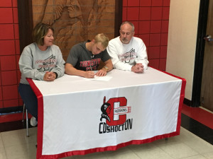 Coshocton senior Nick Kirkpatrick sits with parents Kelly and Keith Kirkpatrick while signing his national letter of intent to pole vault at Youngstown State University. Andrew Everhart | Beacon