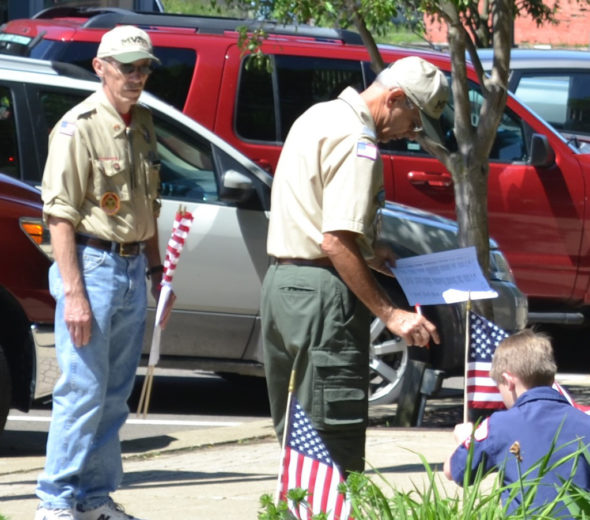 A Boy Scout is pictured placing a flag on the Coshocton Court Square as the name of a veteran who passed away in the last year was read during the Coshocton Memorial Day Service. Jen Jones | Beacon