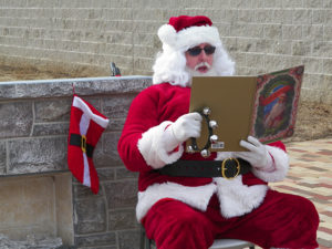 """Santa Claus reads """"Twas the Night Before Christmas"""" to the crowd at the first Our Town Coshocton Christmas event held Dec. 10. Jen Jones 