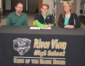 Signing: Nick Wilson, center, signed his letter of intent April 13, at River View High School in the library to do cross country and track at Lake Erie College. Pictured with Nick are his dad Robert and his mom Katina. Beacon photo by Josie Sellers