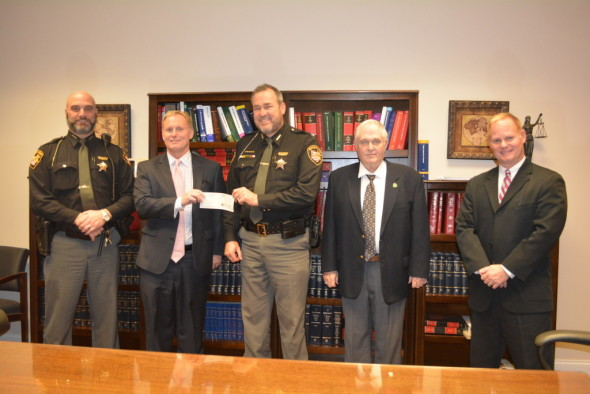 The Skelton family presented a check to the Sheriff's Office on Tuesday, Dec. 22. Pictured left to right are: Lt. Dean Hettinger, Robert Skelton, Sheriff Timothy Rogers, Joseph Skelton, and James Skelton. The $12,500 check will be used to help purchase new Tasers.