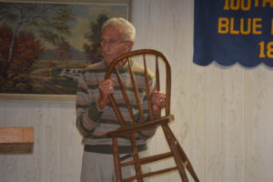 Jim Hoffman displays one of the original chairs that were purchased for the grange in 1896. They were purchased for a cost of $0.20 each.
