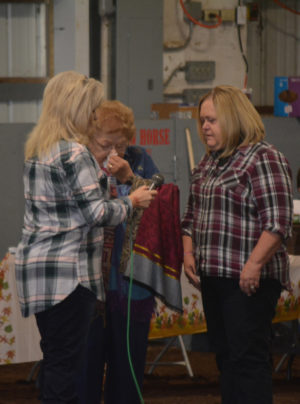 Patti Fischer gives scarves to Janet Fender and Phyllis Wycoff in memory of their husbands, Dennis Fender and Bill Wycoff during the llama show at the fairgrounds on Sunday, Oct. 2. The show was dedicated to their memory. Beth Scott | Beacon