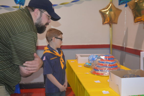 Ryder Milligan shows Kevin Cichon the cake he made for the Cub Scout birthday celebration at the annual Blue and Gold dinner. The cakes were later auctioned off to raise money for the Cub Scouts.