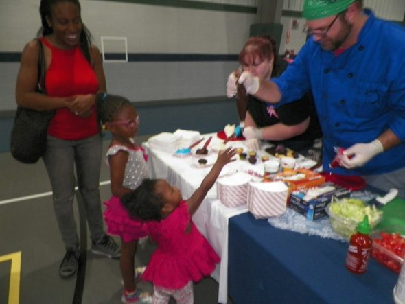 Marlie and Melanie Grant, daughters of Cie and Brandi Grant, carefully choose a cupcake and the frosting to decorate it with at the Responsible Fatherhood Event held at Kids America on June 17.