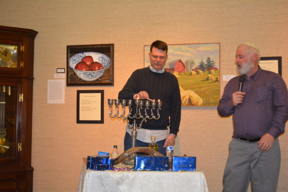 Pastor Brent Heishman lights the menorah during the Celebration of Lights program at the Johnson-Humrickhouse Museum on Saturday, Dec. 20. Robert Specter, pictured on right, is the president of the Rock of Israel Ministries and spoke about the similarities of Hanukah and Christmas.
