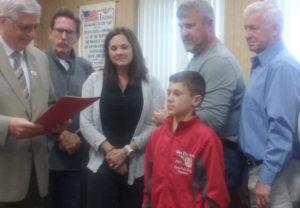 Mayor Steve Mercer, pictured at left, presented Colton Conkle (center) with a proclamation celebrating his Elks National Hoop Shoot title during the May 8 Coshocton City Council meeting. Standing behind them are members of city council. Josie Sellers | Beacon