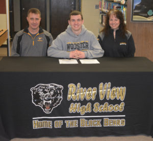 Caden Croft, center, signed his letter of intent to play football at the College of Wooster on Feb. 1 in the library at River View High School. He is pictured with his dad Whit Croft and mother Leslie Croft. Josie Sellers | Beacon