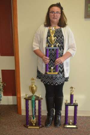 Bridgette Bible is the proud owner of back to back Elks National Soccer Shoot titles. She is pictured here holding her trophy from this year and at her feet are last year's trophy plus the one she won that year for being the highest scorer. Josie Sellers | Beacon