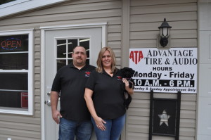 Anniversary: Randy and Julie Leist, owners of Advantage Tire & Audio, are pictured with Marlee in front of their showroom and office. They are celebrating almost two years in business and are located at 19970 County Road 6 in Coshocton. They are open from 10 a.m. to 6 p.m. Monday through Friday. You can contact them at 740-295-9200. Beacon photo by Mark Fortune