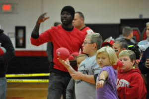 Fun times: Nine year old Skyla Johnson gets ready to toss the football at a hole that was cut into the side of a plastic 55 gallon barrel at the second annual Coshocton County Fatherhood Initiative All Pro Dad's Breakfast held Saturday morning, Oct. 17 at Coshocton High School. That's Cie Grant, the featured speaker and member of the 2002 Ohio State Buckeyes National Championship team in the background. Kids, dads and family members enjoyed breakfast and then the kids could kick soccer balls, shoot hoops or try the football toss in the gymnasium prior to Grant speaking. BEACON PHOTO BY MARK FORTUNE