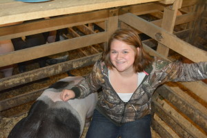 Hog project: Bailey Fry smiles with her pig Oliver. This was her ninth year taking a hog project to the Coshocton County Fair. Beacon photo by Josie Sellers