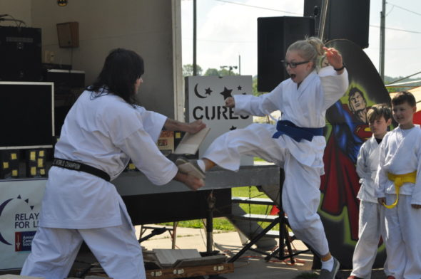 Students from Jon McFarland's Champion Martial Arts classes took turns breaking boards with messages written by area cancer survivors on Saturday morning, May 13 at the fairgrounds during the 22nd annual Relay for Life event. Mark Fortune | Beacon