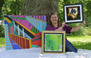 Katie Werner of Coshocton is pictured with a few pieces of her artwork. She is taking commissions for art pieces from the community starting this month. Artwork in the photo is not for sale.