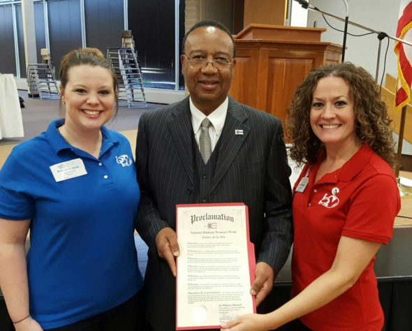 Breanne Smith (left) and Emily McBurney (right) are pictured with City County president Cliff Biggers as he presents a proclamation from Mayor Steve Mercer for National Business Women's Week.