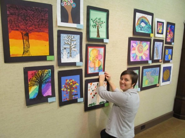 Staff member Jenn Bush puts up the Playground of Color exhibit at the Johnson-Humrickhouse Museum. The exhibit features more than 300 pieces created by local student artists grades kindergarten through sixth grade.