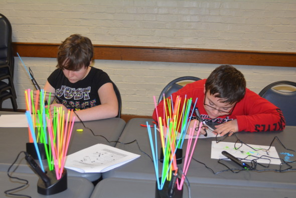 Jaidyn Brink and Lukas Sycks experiment with the new 3Doodlers the Coshocton Library recently purchased for the Maker's Space Club which will meet the first Tuesday of each month.