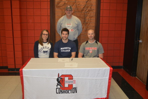Coshocton High School senior Zach Michael, center, signed to play football at Marietta College. Pictured with him is his mom Monica and dad Fred. Behind them is CHS Head Football Coach Jim Woodrum. Josie Sellers | Beacon