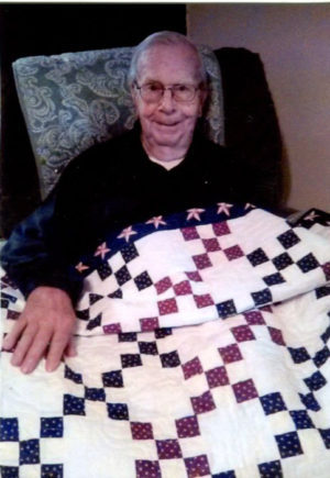Dick Scherer smiles while showing off the patriotic quilt he received from a project worked on by the Coshocton Elks Lodge 376 and the Coshocton Canal Quilters. Contributed | Beacon