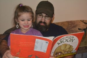 Sophia Sellers, a participant in the Dolly Parton Imagination Library program, is pictured reading with her father, Eric Sellers. Contributed | Beacon
