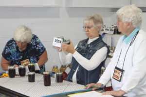 Vicki Bechtel, center, carefully exams canned goods during judging on Sept. 28 in the art hall at the Coshocton County Fairgrounds. Josie Sellers | Beacon