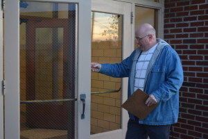 Tour: Conesville Elementary School Principal Joel Moore demonstrated a safety issue with one of the building's doors during a tour he gave on Nov. 24 to representatives of community agencies. Beacon photo by Josie Sellers