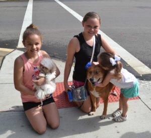 Rachel Levy, holding Gucci, and Hailey Tubbs with Suzie (who is getting a big hug from Lily Tubbs) are enjoying spending time together and showing off their dogs at the dog parade during the First Friday Celebration on July 7. Jen Jones | Beacon