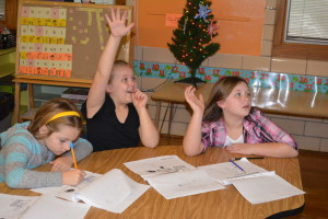 Lesson: Maria Goodman, Draven Dupler and Lacee Garvin listen to a lesson on Christmas in France during Union Elementary School's Holidays Around the World. In France Santa Claus goes by the name of Père Noël and he puts gifts in children's shoes instead of stockings. Beacon photo by Josie Sellers