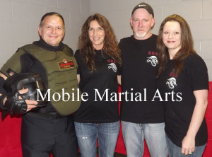 """Self defense: Brad Birkhimer and James Wilson are both trained martial artists who want to use their knowledge to help people learn the basics of self defense. """"We want to teach them how to be aware, avoid situations and if they find themselves physically confronted be able to end it in a very short fashion,"""" Birkhimer said. Their self defense class is designed for people of a variety of ages and levels of physical ability and they also are working on a class just for children. """"We want to give people the confidence and ability to not be afraid of the unknown,"""" Wilson said. Because their business is mobile, they also plan to host classes at a variety of locations. To learn more about the new Mobile Martial Arts business, visit their booth at the Health, Safety, and Wellness Expo, which will be held from 9 a.m. to 1 p.m. Saturday, Jan. 17, at Kids America. Pictured from left are Birkhimer, his wife Denise, Wilson and his wife Billie. Photo contributed to The Beacon"""
