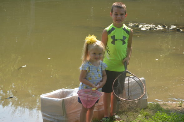 Jace Coffman, 6, and his sister Allie Coffman, 3, had the pleasure of helping the Coshocton City Recreation Department dump 1,000 fish into a pond by Kids America, where the public can now fish. Their Grandpa Coffman works for the city recreation department and invited them to come help with the project on July 18. Josie Sellers | Beacon