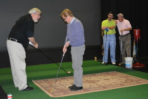 "Theater: Shane Pyle gives Nathan Mayse some golf tips while practicing a scene from ""The Foursome."" Watching the action are Jeff Wherley and Denny Blanford. The four actors will perform the Footlight Players latest production at 8 p.m. Friday and Saturday, March 6-7, 13-14, 20-21, at Triple Locks Theater, 685 N. Whitewoman St. Beacon photo by Josie Sellers"