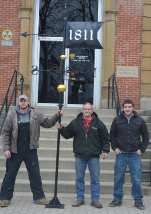 Brad Birkhimer (center) was asked to create a weathervane for the Coshocton County Courthouse. Pictured with him are his sons BJ (left) and Richard (right) who Brad said helped some with the assembly and the design, but were definitely going to help him mount it to the top of the courthouse. Josie Sellers | Beacon
