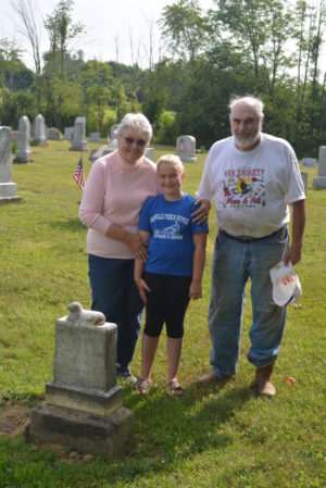 Mary Ann and Jim Williamson stand by the gravestone that spurred Jim's interest in getting markers at the cemetery in Newcastle that had fallen over straightened back up. Pictured with them is Trista Wilson, whose father Eric volunteered to help with the project.